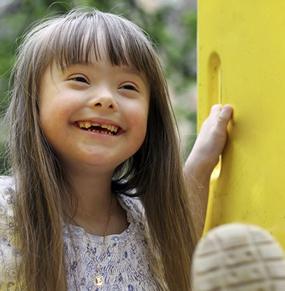photo of a girl with downs syndrome with a terrific smile playing at a playground