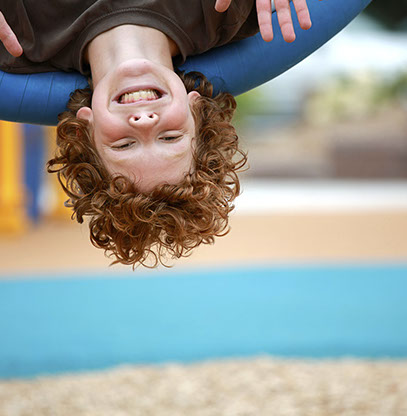 photo of a boy smiling and waving, upside down, on a playground