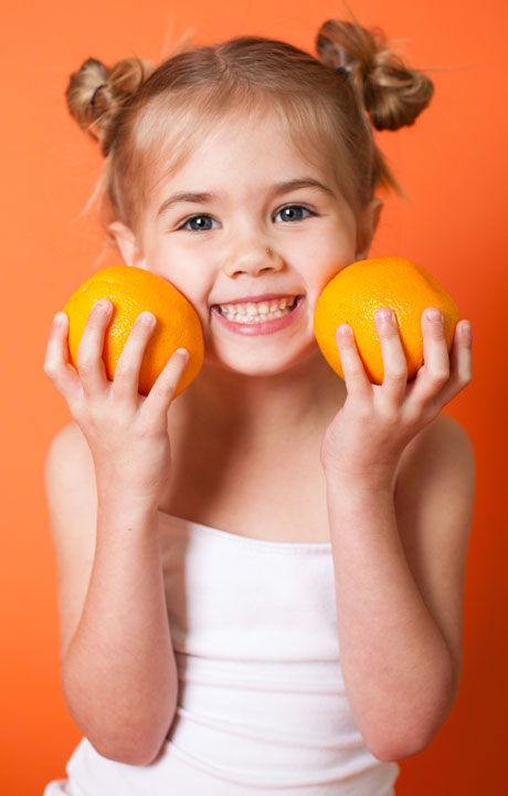 Photo of a smiling girl holding up two oranges
