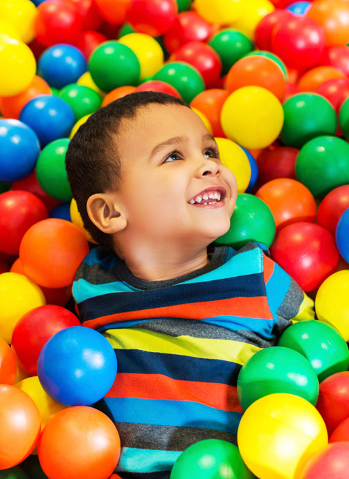 photo of boy swimming in a playground full of colorful balls
